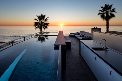 rooftop deck with pool and view of ocean