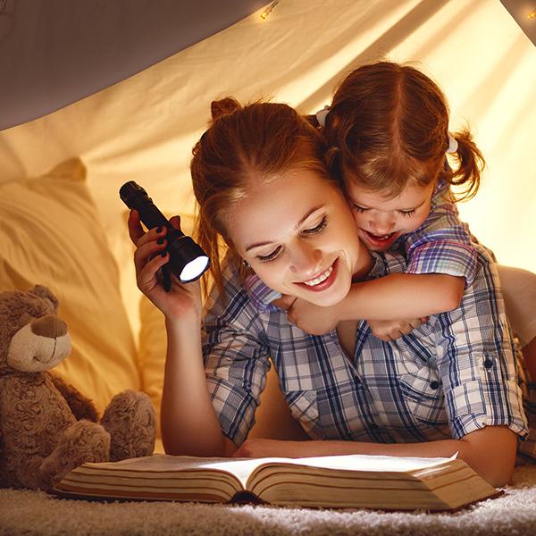 Mom reading a book by flashlight