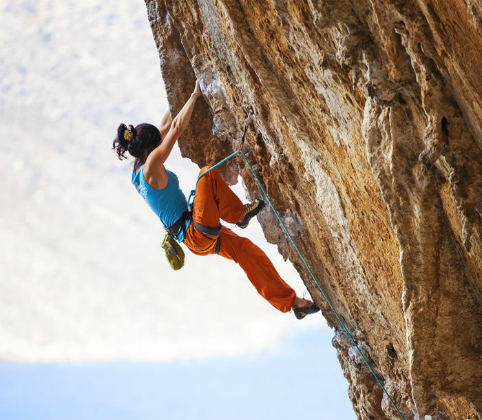 Woman climbing a rock face with ropes