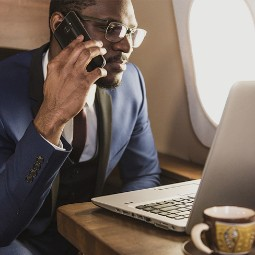 A businessman working on a plane with his laptop and phone