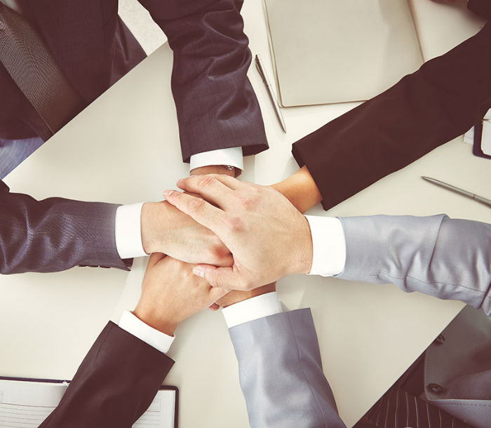 Several business people with their hands connected