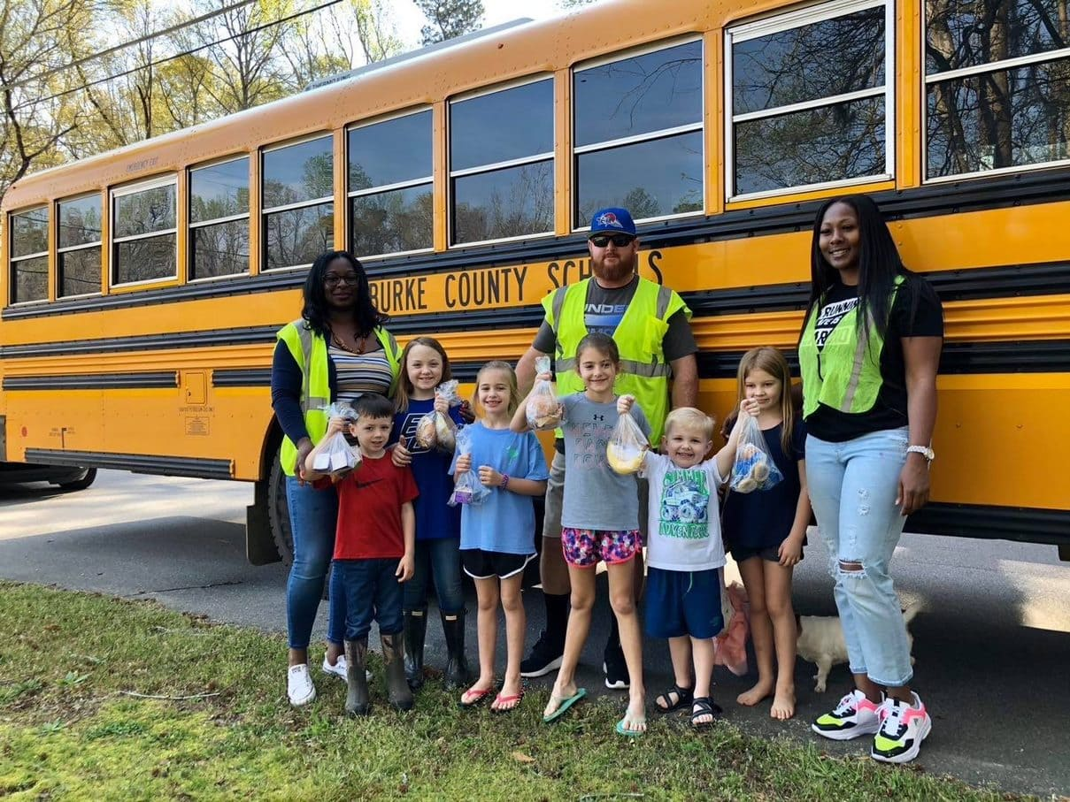 Kids holding lunches standing in front of school bus with 3 school bus drivers in safety vests.