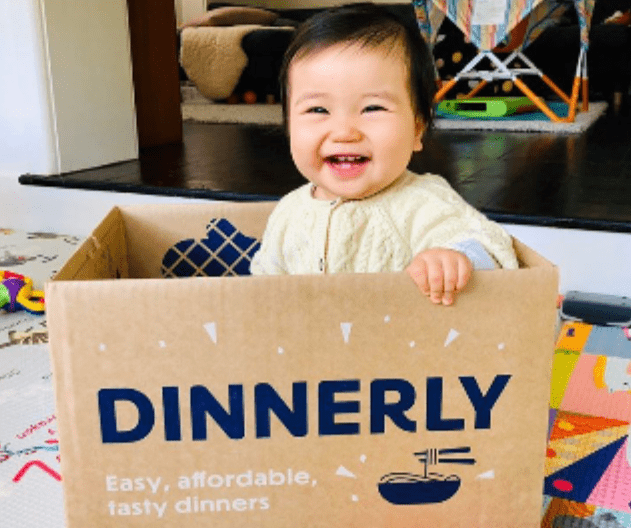 Smiling baby sitting inside a cardboard box with Dinnerly meal kit label on it