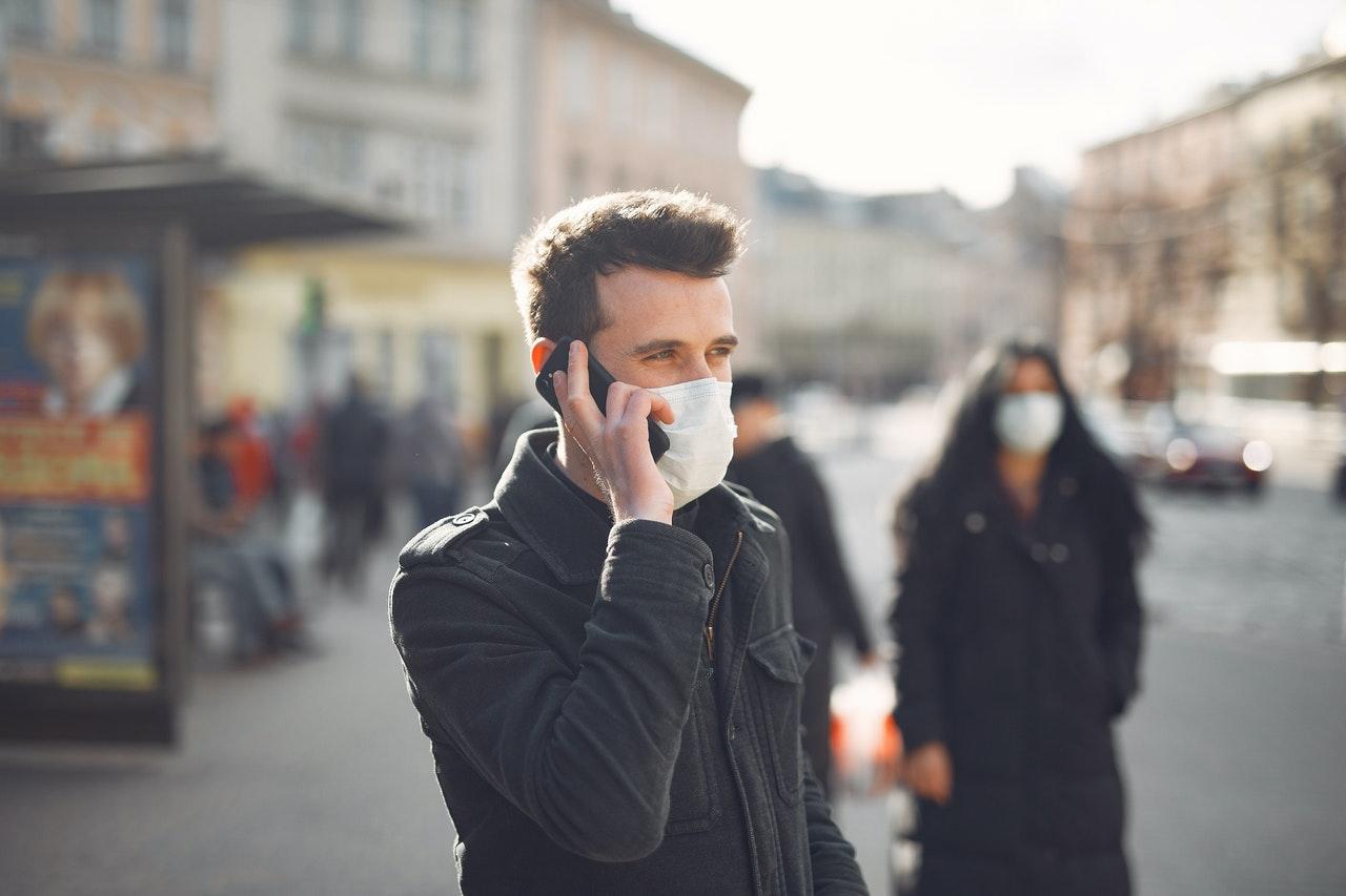 Mężczyzna w amseczce rozmawia przez telefon komórkowy na ulicy.