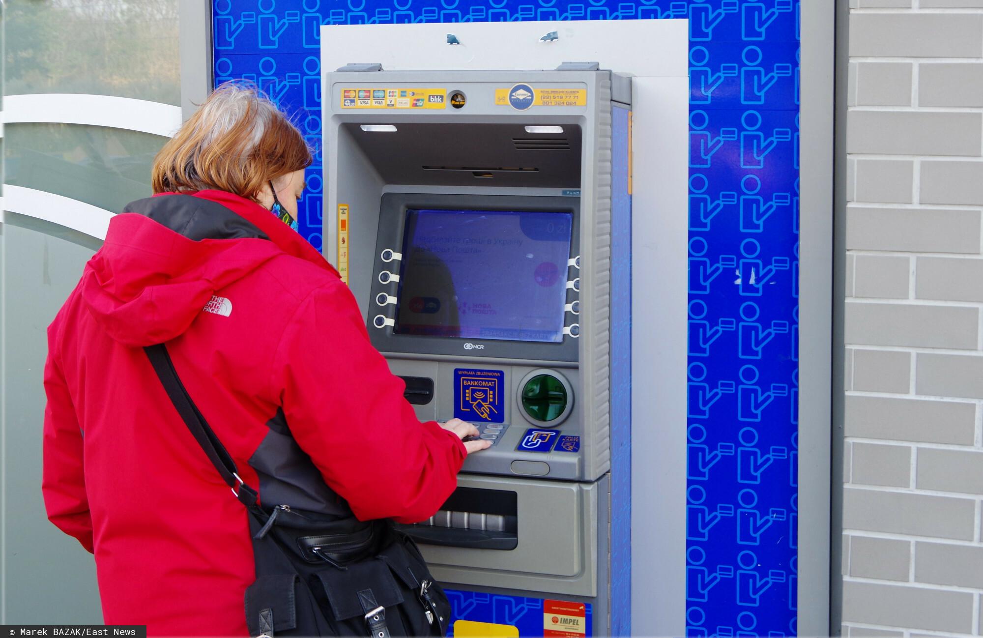 Kobieta wypłaca środki pieniężne z bankomatu - materiał ilustracyjny