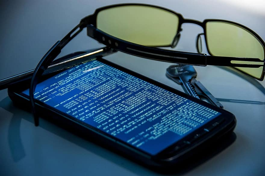 Smartfon z kodem na ekranie, okulary, klucze.