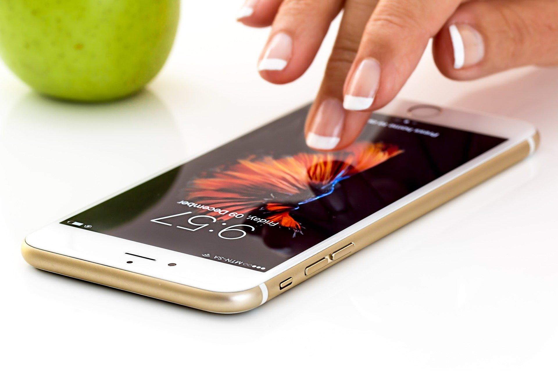 Kobiecy palec trzymany nad leżącym smartfonem