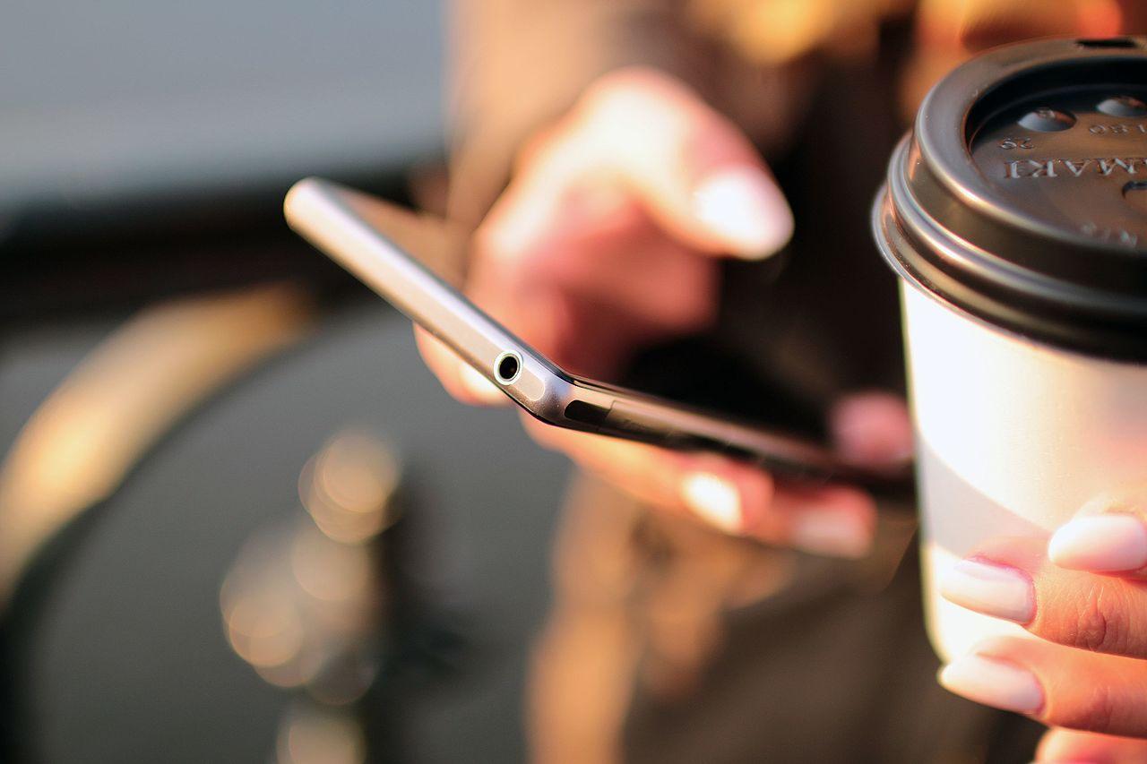 Smartfon trzymany w kobiecej dłoni, obok kubek z kawą.