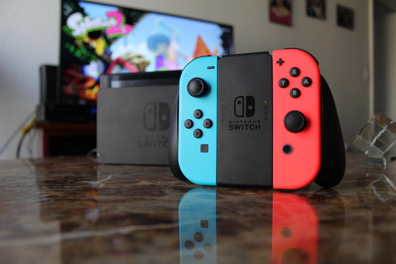 Konsola Nintendo Switch na stole. W tle ekran telewizora z włączoną grą.