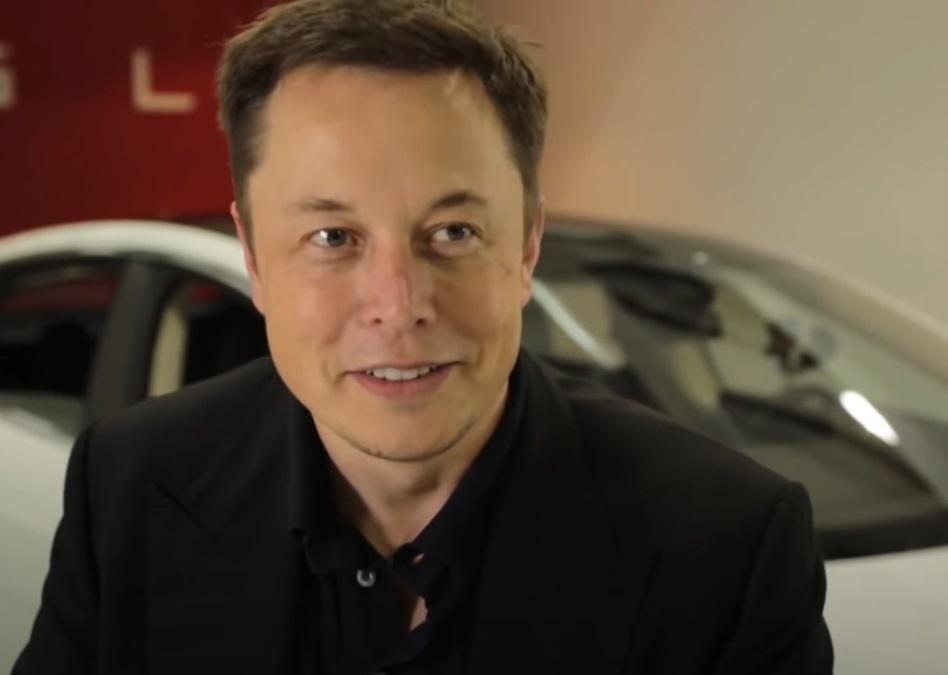 Uśmiechnięty Elon Musk z autem w tle