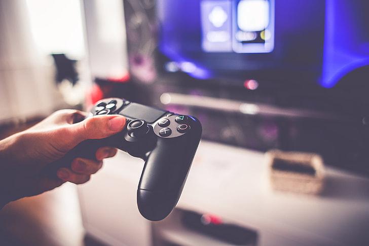 Kontroler DualShock do Play Station 4 trzymany w dłoni.