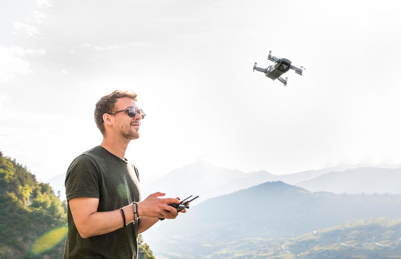 Mężczyzna sterujący dronem w górach.