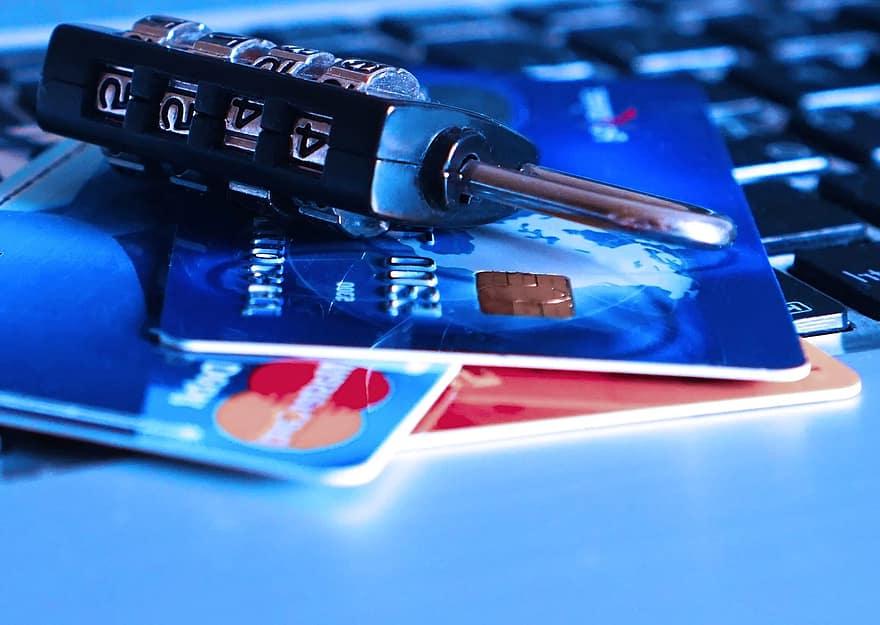 Karty kredytowe na klawiaturze laptopa i kłódka sugerująca zabezpieczenie.