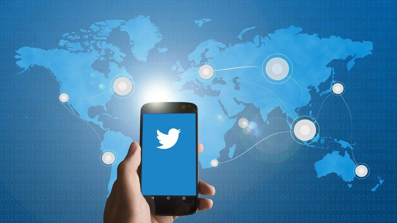 Telefon z logo Twittera trzymany w dłoni na tle niebieskiej mapy świata
