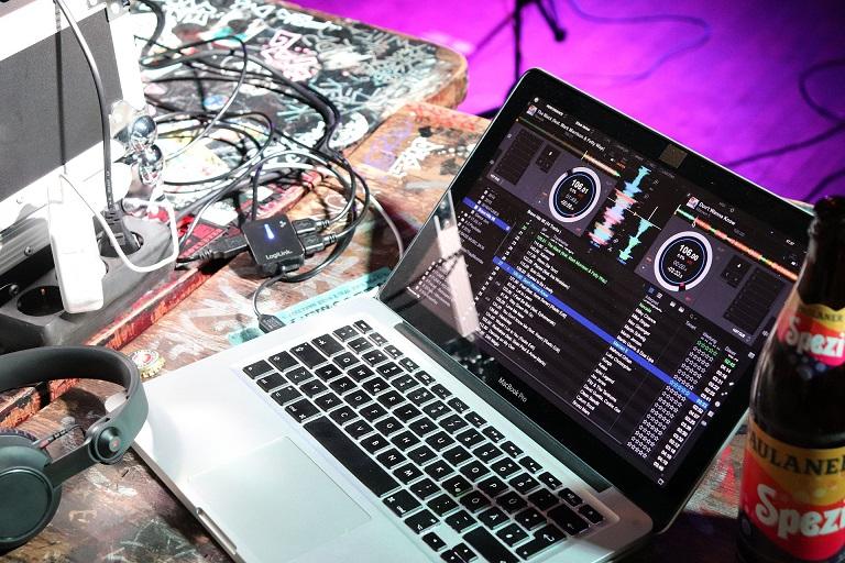 Laptop z włączoną aplikacją muzyczną. Kable, przedłużacze, słuchawki.