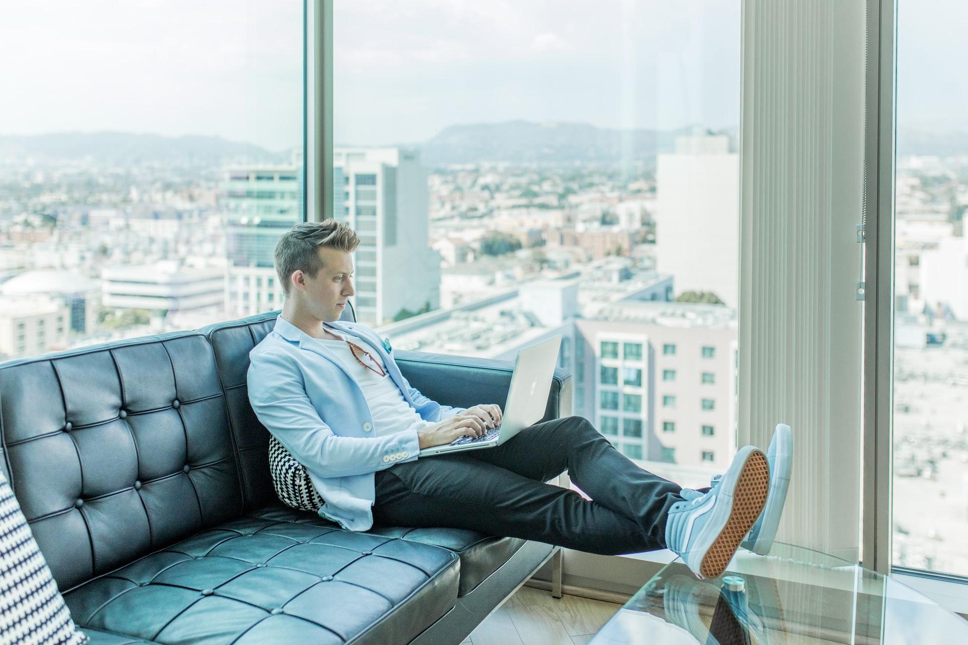 Młody człowiek na kanapie z laptopem na nogach