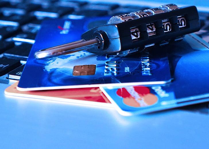 Karty kredytowe z kłódką leżące na klawiaturze laptopa.