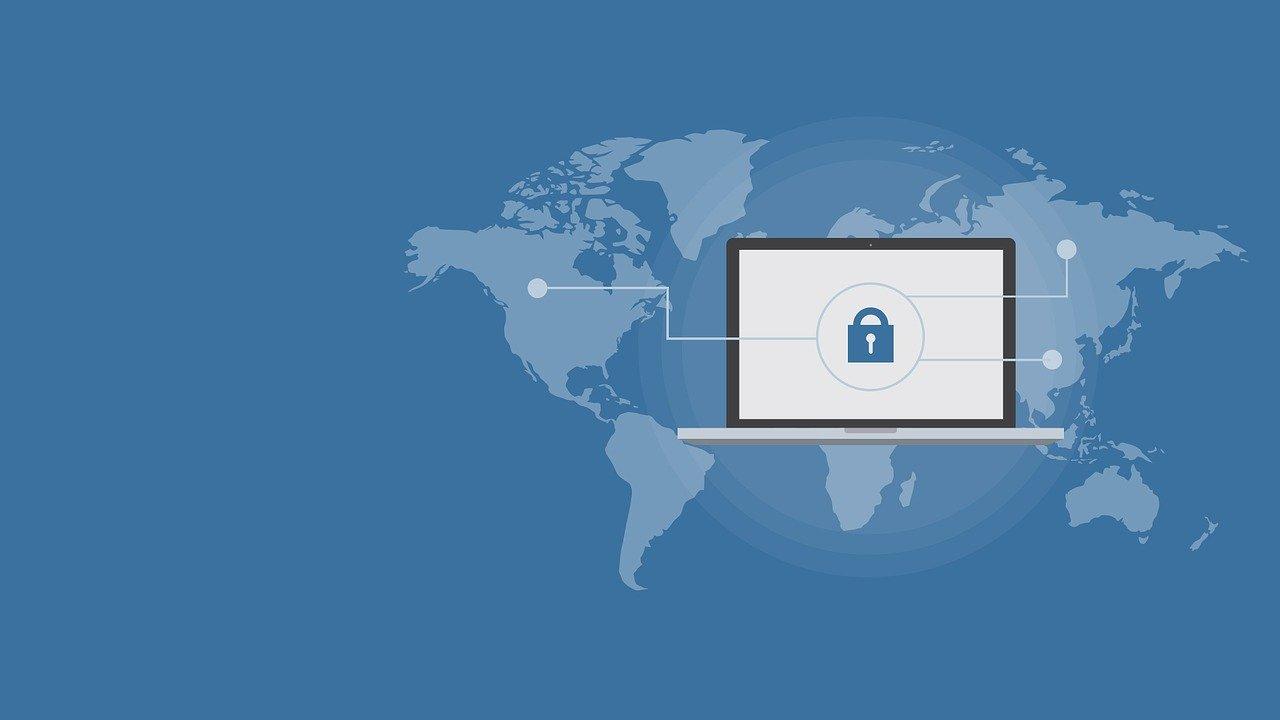 Laptop z zabezpieczeniami na tle mapy świata.