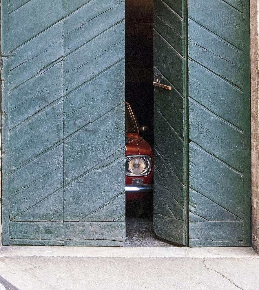 Otwarte drzwi od garażu, w środku stary samochód.