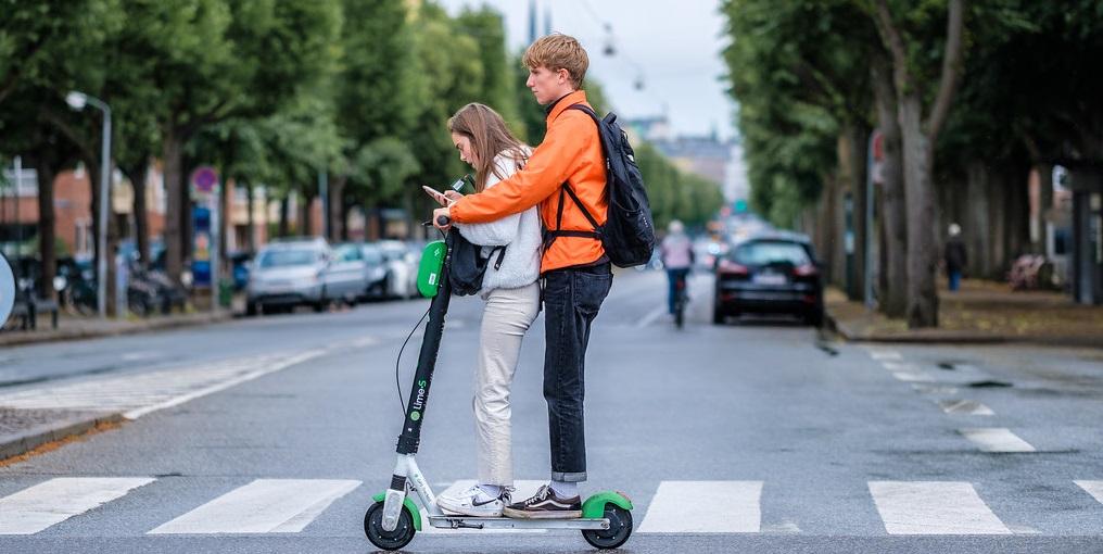 Para jadąca na hulajnodze elektrycznej przez przejście dla pieszych