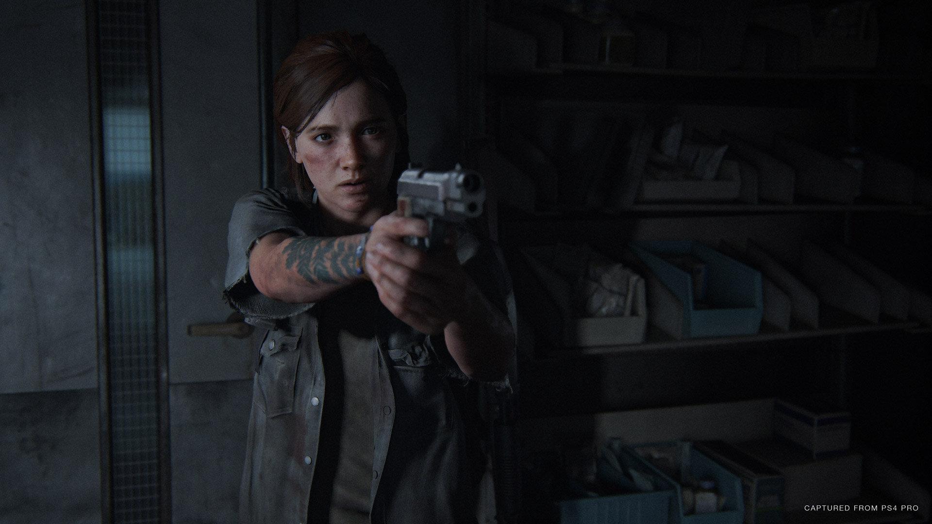 Screen z gry The Last of US Part Two. Główna bohaterka celuje z broni w ciemnym pomieszczeniu.