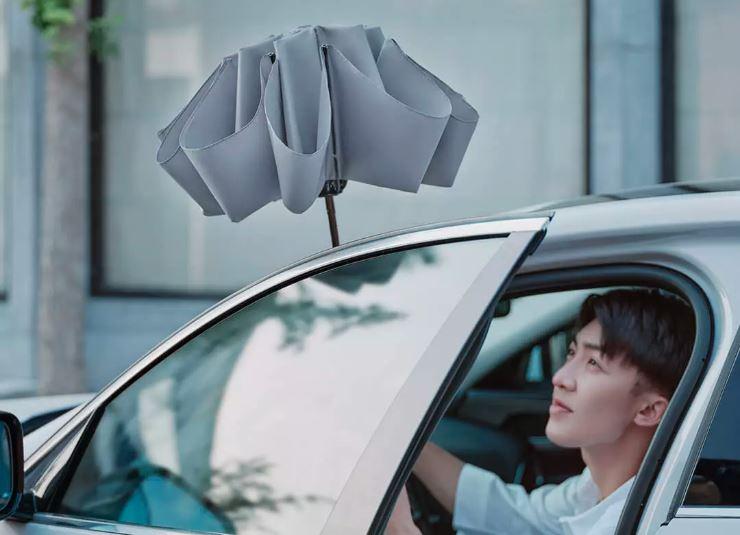 Parasol Xiaomi złożony odwrotnie. Mężczyzna wysiadający z samochodu.
