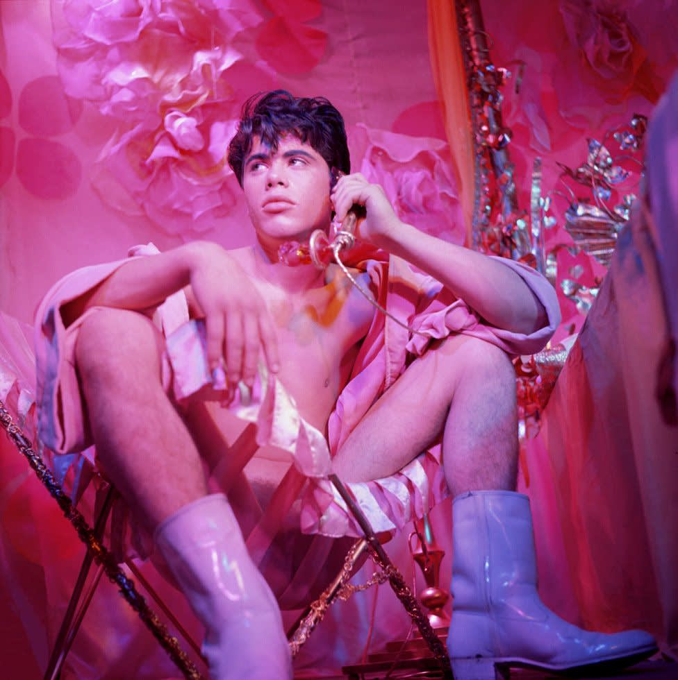 Bobby kendall seated in chair holding phone from    pink narcissus