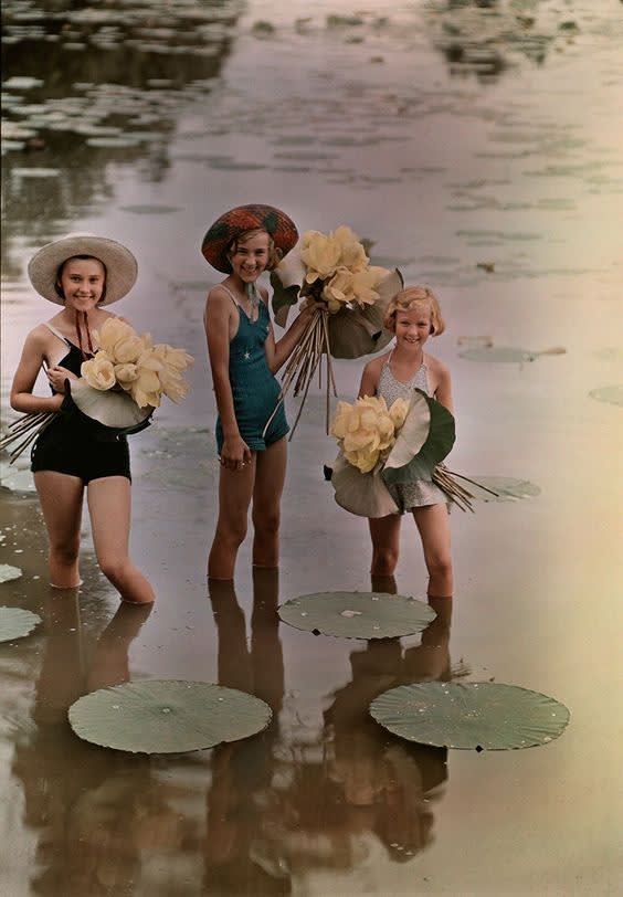 Girls standing in water holding bunches of american lotus  amana  iowa  1938.