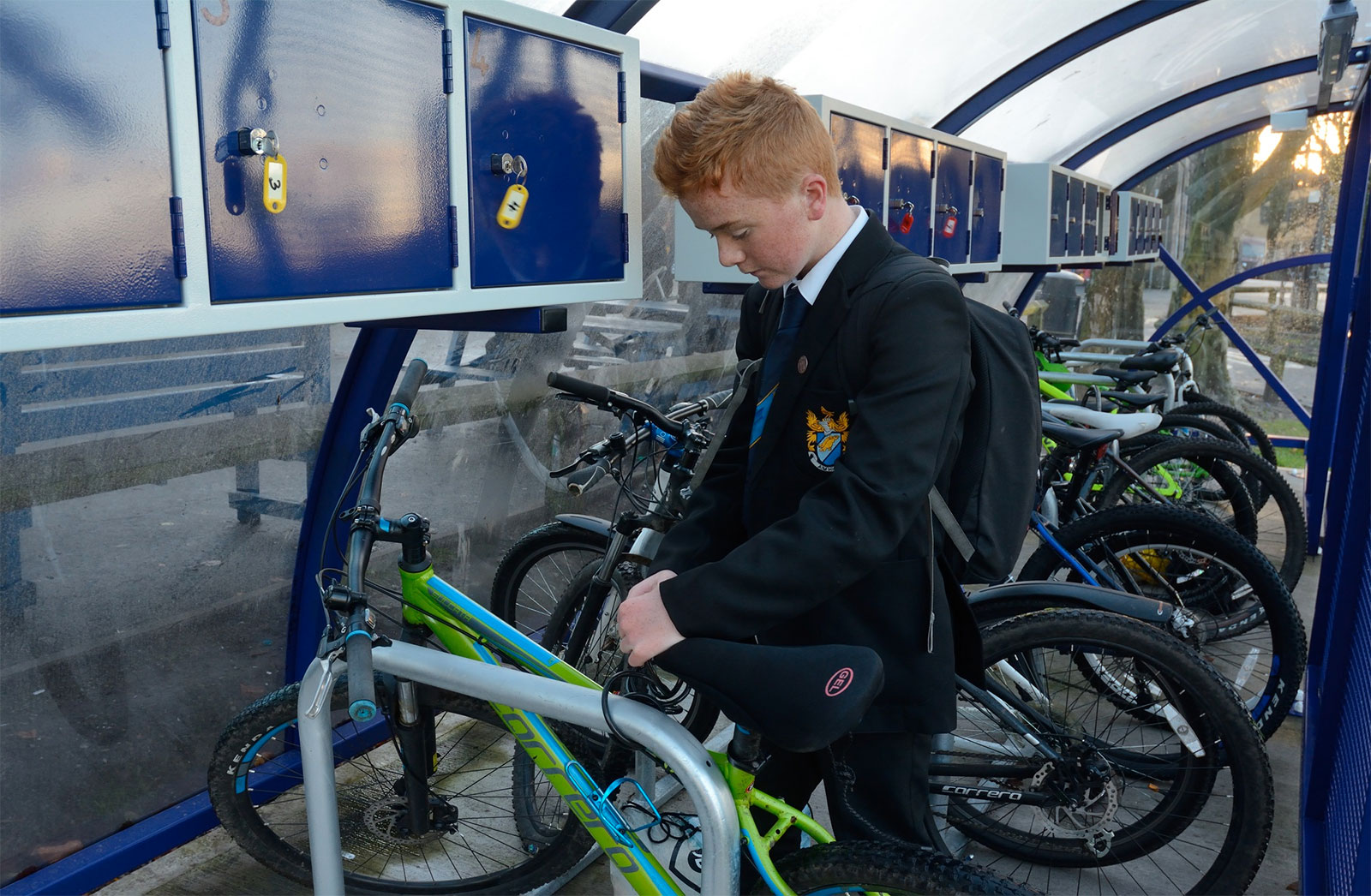 PIC 3 West Hill pupil locking his bike in one of the new cycle parking shelters