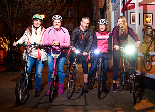 Group of cyclists cycling at night time outside cycle shop in Manchester