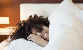 Happy woman taking it easy in a lush hotel bed, knowing she won't be downgraded in all of 2021.