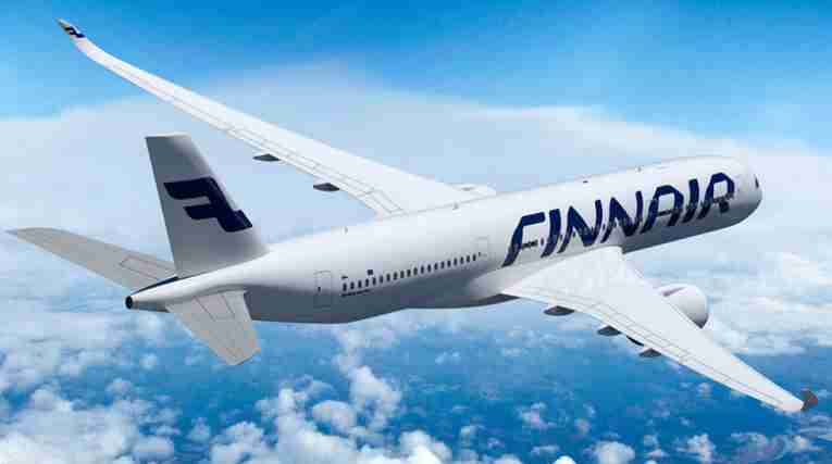 Et Finnair-fly flyr over blå himmel.