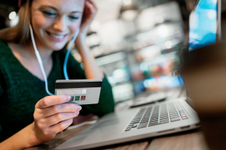 woman-smiling-laptop-holding-card-nordic-choice-club-mastercard