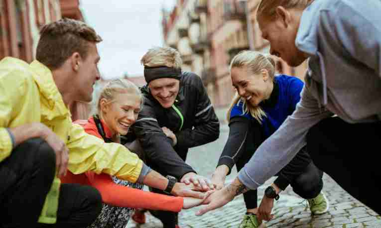 A group of runners squatting with their hands in a circle