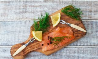 Cured salmon with dill and lemon on a wooden cutting board.