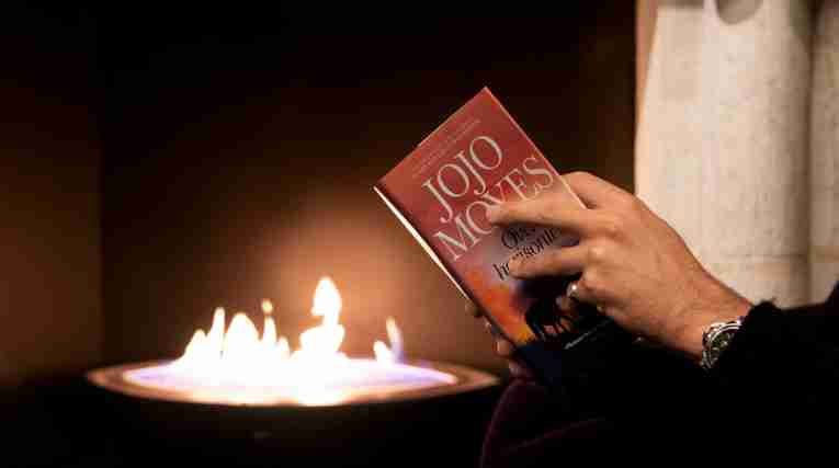Strawberry Publishing, man reading book in front of fireplace