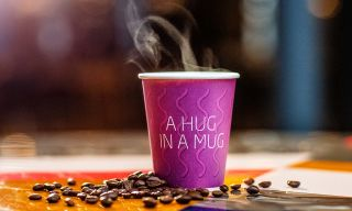 "A paper cup of warm coffee with the text ""A hug in a mug""."