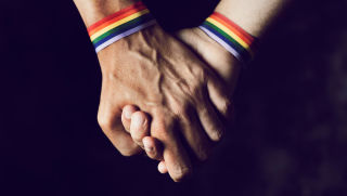 Close up on gay couple holding hands.