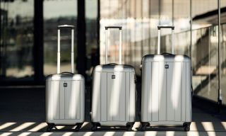 Three silver Rizzo suitcases in a row.