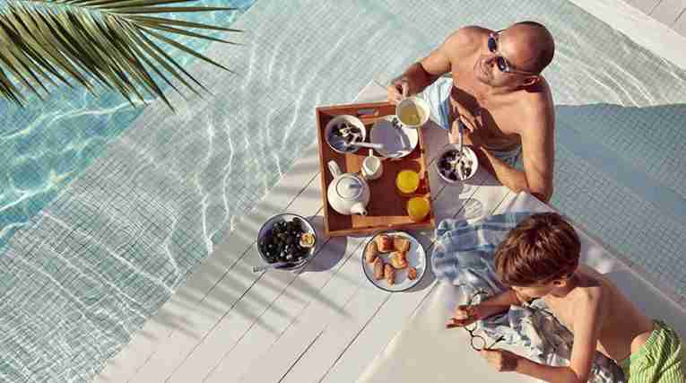 Man and child eating breakfast by the pool