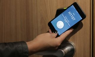 A hotel guest unlocks the door with a mobile key