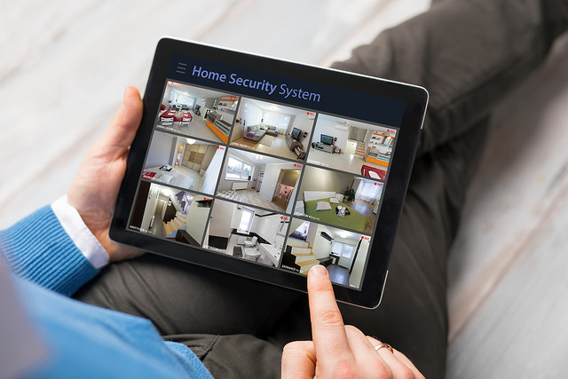 man-on-tablet-looking-at-security-system