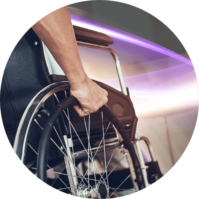 A man is holding a wheel of his wheelchair