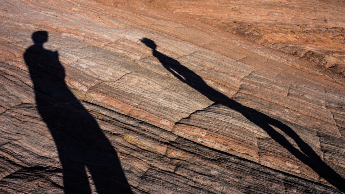 Hiking over the orange slick rock in Zion National Park