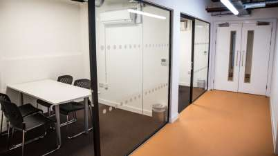 a corridor with modern meeting rooms