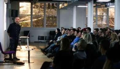 Photo taken during event of a man speaking to an audience.