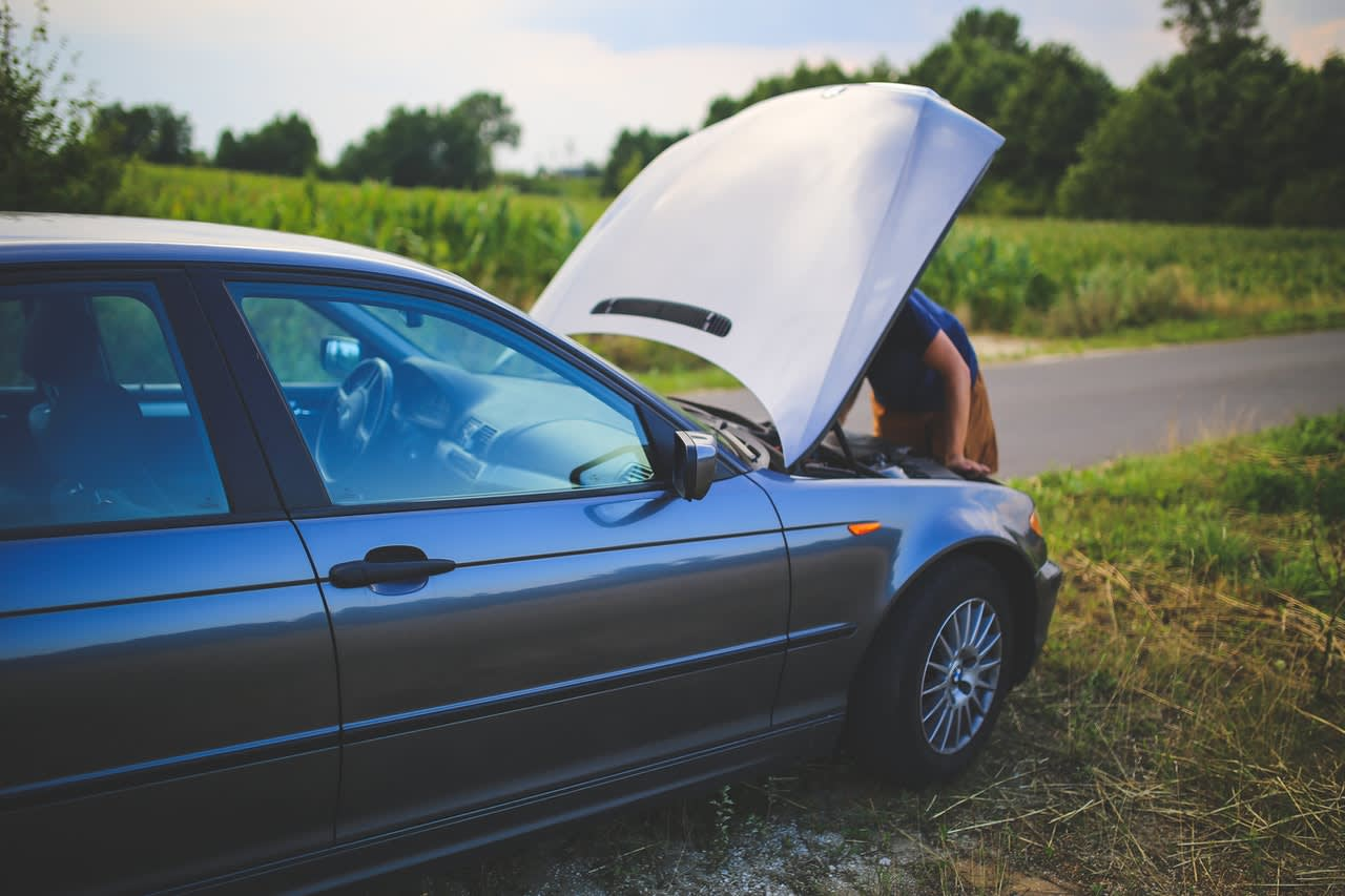 A car on the side of a road with its bonnet up as an owner seeks to identify the problem which has caused it to breakdown