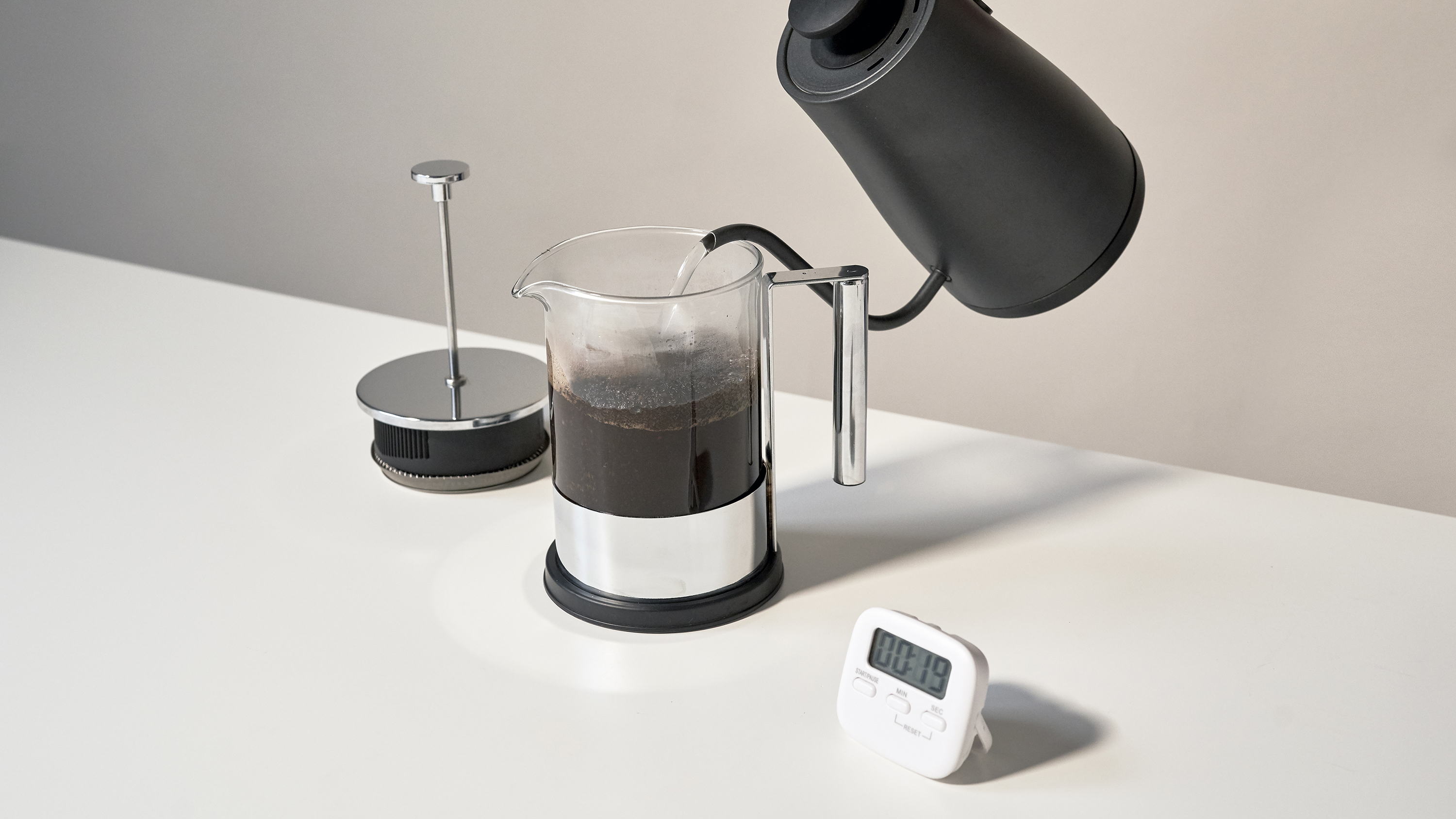 Making coffee with a French press, using a goose-neck kettle and a timer.