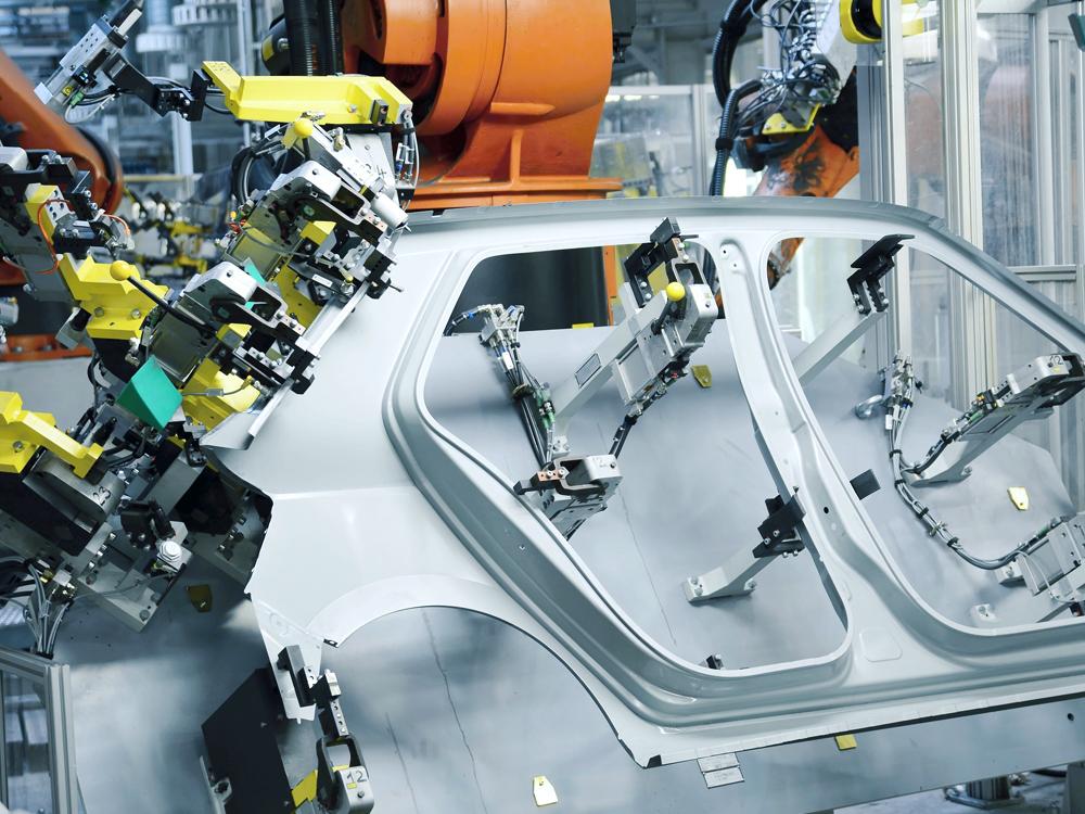 Industrial Robots weld a car door.