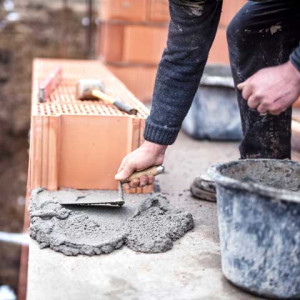 Construction worker using trowel and cement for installing the brickwork - Mauermörtel, Mauern